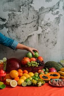 さまざまな種類の新鮮な有機フルーツをテーブルから青リンゴを取っている女性の手