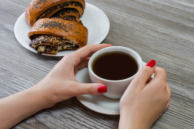 Руки женщины касаются чашки чая, булочки с маком на заднем плане, женщина перекусывает на работе