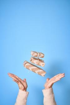 Руки женщины пытаются поймать подарочную коробку. рождество или новый год украшен подарочной коробке.
