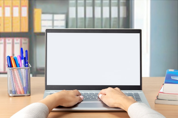 Woman's hands typing on computer laptop with white blank screen at office. student e-learning distance training course study work at home office.