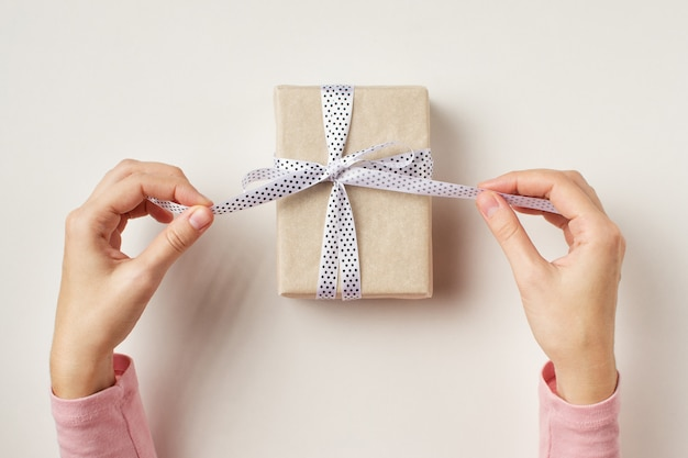 Woman's hands untie bow on gift box on white background, top view