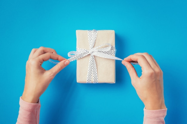 Woman's hands untie bow on gift box