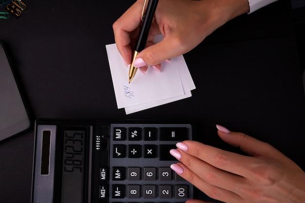 机の上の電卓を使用して女性の手