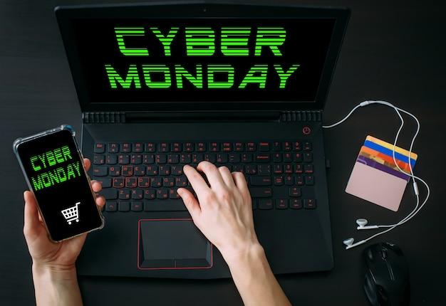 Руки женщины, использующие ноутбук и смартфон для покупок в интернете дома во время распродаж cyber monday