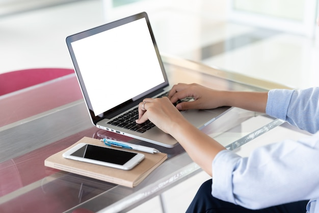 Woman's hands using laptop with blank screen on desk in home office