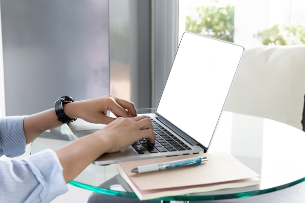 Woman's hands using laptop with blank screen on glass desk in home office