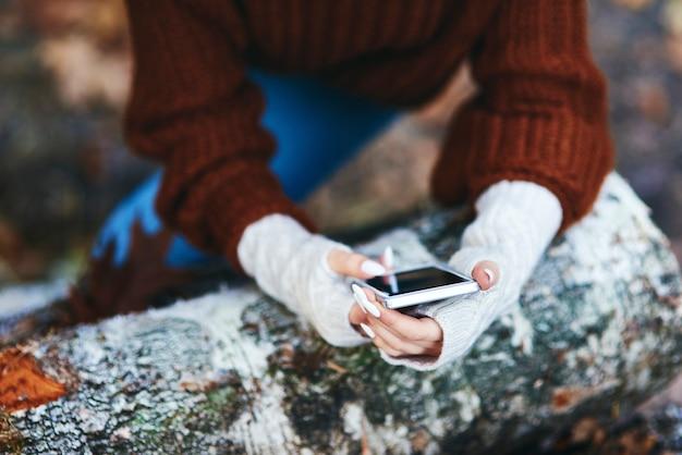 Руки женщины с помощью мобильного телефона в осеннем лесу