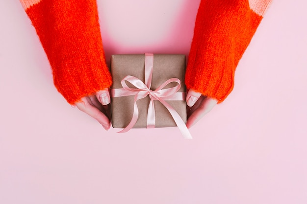 Woman's hands in warm knitted sweater with manicure hold gift box wrapped with craft paper and pink ribbon on pink.