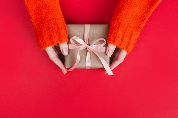 Woman's hands in warm knitted sweater with manicure hold gift box wrapped with craft paper and pink ribbon on red.