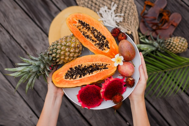 Женские руки с большой тарелкой свежих экзотических фруктов.
