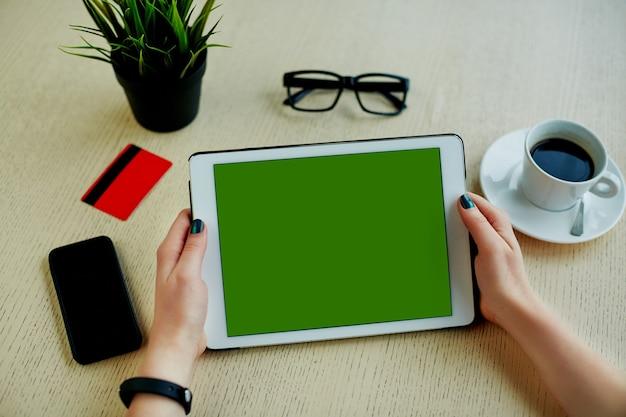 녹색 태블릿, 신용 카드, 안경, 휴대 전화 및 테이블, 프리랜서 개념, 온라인 쇼핑, 평면 누워에 커피 한잔 들고 어두운 매니큐어와 여자의 손.