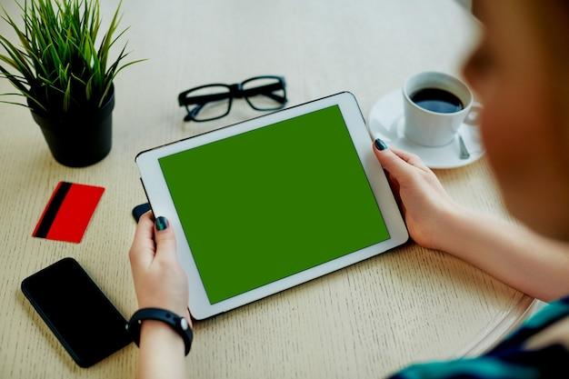 녹색 태블릿, 신용 카드, 안경, 휴대 전화 및 테이블, 온라인 쇼핑, 평면 누워 커피 한잔 들고 어두운 매니큐어와 여자의 손.