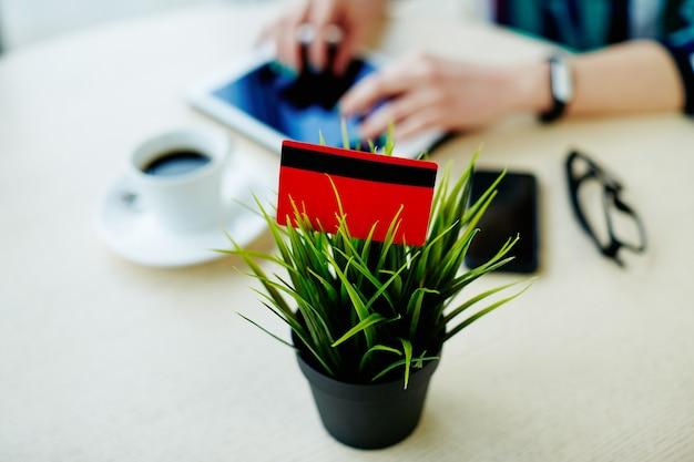 タブレット、携帯電話、テーブルの上のコーヒーのカップで作業するダークマニキュアの女性の手、クレジットカードのクローズアップ写真、フリーランスのコンセプト、オンラインショッピング、フラットレイ。