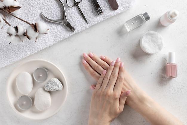 マニキュアツールの壁に繊細なピンクのマニキュアで女性の手。ネイルサロンとスパ。白いコンクリートの壁、トップビュー。
