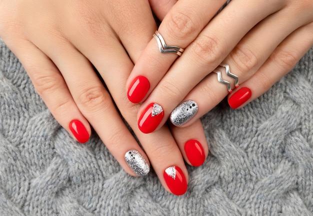 유행 빨간 매니큐어와 여자의 손입니다.