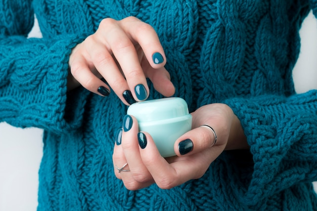 Woman's hands with turquoise manicure hold a jar of cream