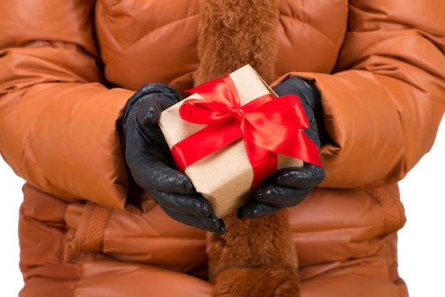 Woman's hands with winter gloves holding a christmas red gift box.
