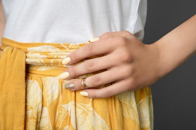 黄色の光沢のあるネイルデザインの女性の手。