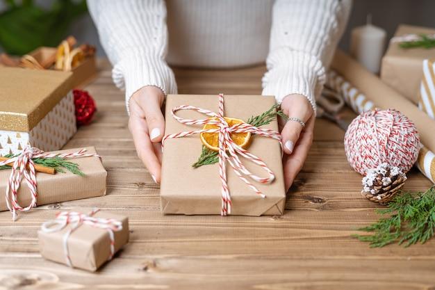 Руки женщины, упаковка рождественский подарок