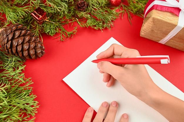 Женские руки пишут письмо на рождество