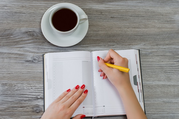 Woman's hands writing information in a notepad. cup of tea is on the background. overhead view, copy space