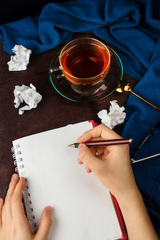 Woman's hands writing on a notebook with blank page with cramped paper, glasses and cup of tea