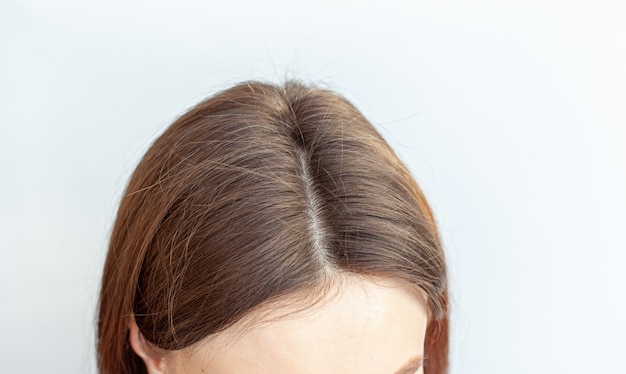 A woman's head with a parting of gray hair that has grown roots due to quarantine