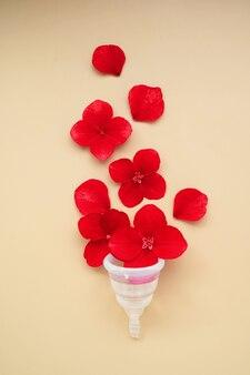 여성의 건강 개념입니다. 붉은 꽃이 있는 월경 투명 컵. 평면도.