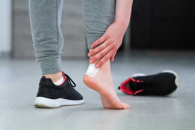 Woman's heel with white medical adhesive plaster from calluses during wearing a new shoe. skin care feet and prevention of calluses and corns