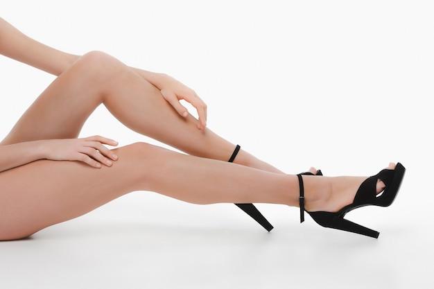 Нога женщины и туфли на высоком каблуке на белом полу студии