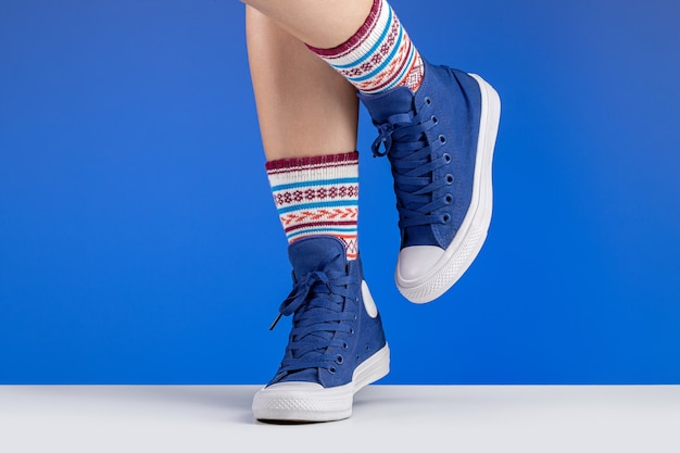 Woman's legs in blue sneakers and colored socks with ornaments, blue background. sports and recreation.