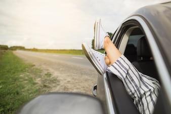 Woman's legs dangling out a car window parked on roadside