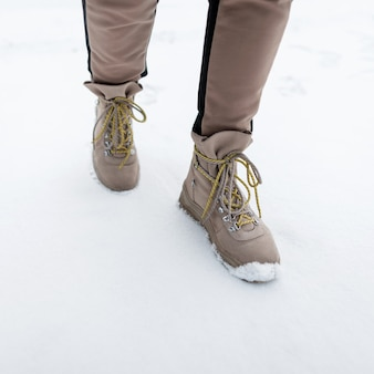 Woman's legs in fashionable pants in stylish winter brown leather boots on the backdrop of snow. fashion girl walk outdoors. close-up.