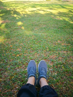 Woman's legs in grey shoes sit on dry leaves