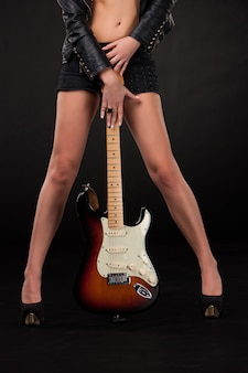 Woman's legs and  hands with electric guitar