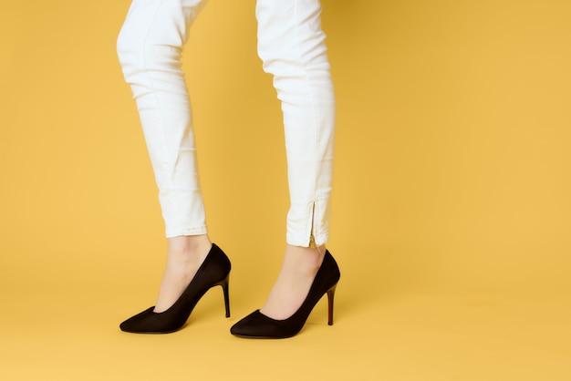 Ноги женщины в черных туфлях на высоких каблуках