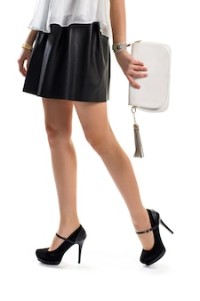 Ноги женщины в черной юбке. белая сумочка и темные каблуки. новые часы и золотой браслет. привлекательная одежда с аксессуарами.