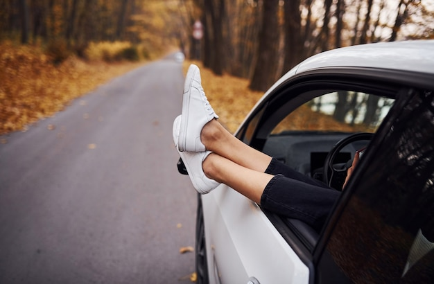 Woman's legs is off the car window. modern brand new automobile in the forest.