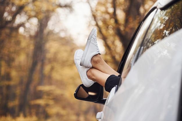 Ноги женщины от окна машины. современный новый автомобиль в лесу.