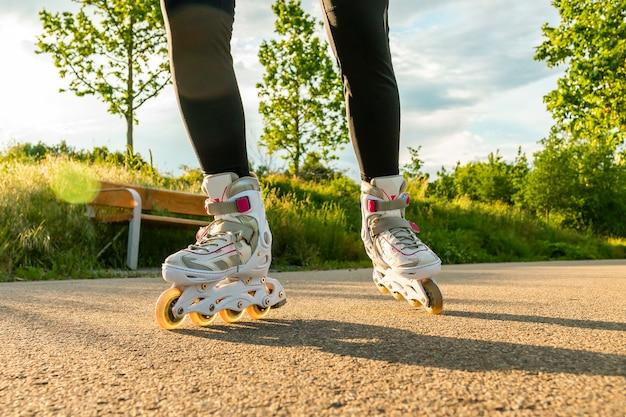 晴れた日にローラーブレードで女性の足。パス上の白いインラインスケートのクローズアップショット。