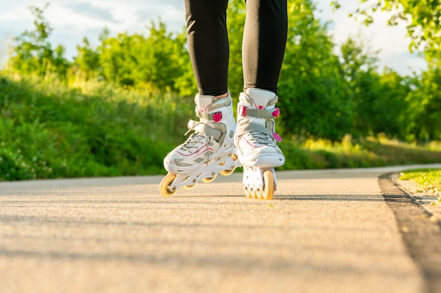 Woman's legs with white roller blades at sunny day on asphalt road.