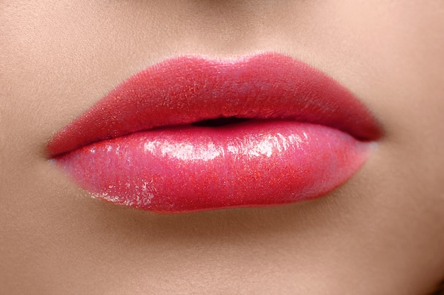 Woman's lips covered with red lipgloss.