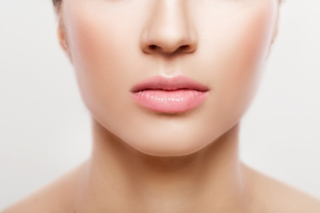 Woman's lips with natural make up on white background, close up