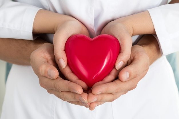 Woman's and man's hands holding red heart together. love, assistance and healthcare concept