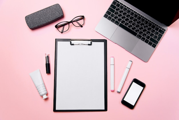 Woman's pink office desk with clean sheet of paper with free copy space, laptop, phone with blank white screen, a cream, lipstick, eyeglasses and supplies background