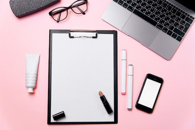 Woman's pink office desk with clean sheet of paper with free copy space, laptop, phone with blank white screen, a cream, lipstick, eyeglasses and supplies background.