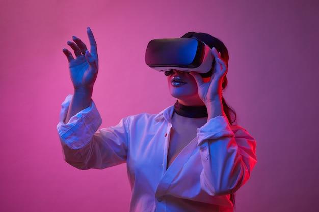 青の背景にネオンライトでvrメガネで遊んでいる女性。バーチャルリアリティ体験をしながらオプションを選択するvrゴーグルの女の子。