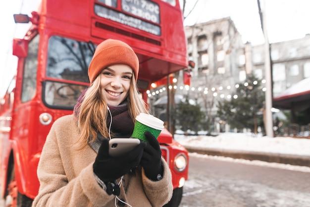 따뜻한 겨울 옷을 입은 여성의 초상화는 도시의 배경에 대해 그녀의 손에 커피 한 잔과 스마트 폰으로 서 있습니다.