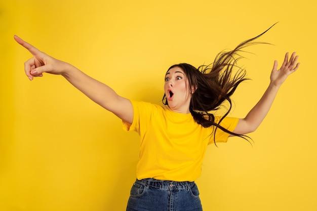 노란색 스튜디오 벽에 고립 된 여자의 초상화