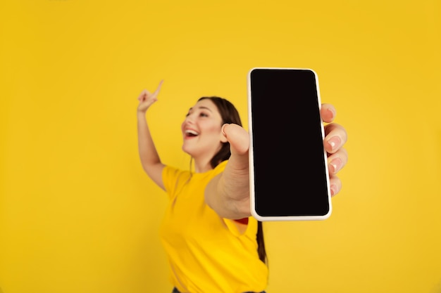 Woman's portrait isolated on yellow studio wall